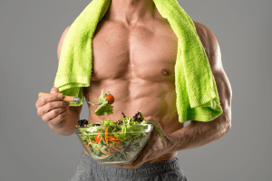 Powerful athletic man with great physique eating a healthy salad