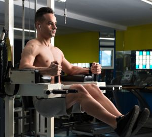 Muscular young man exercising the abs on the machine