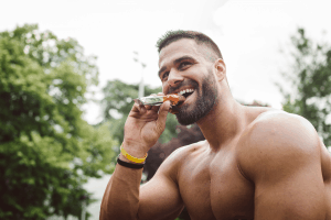 Man is eating a protein bar