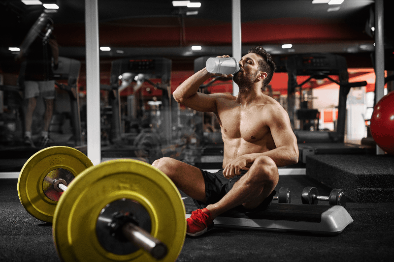 Handsome muscular guy resting and drinking water at the gym