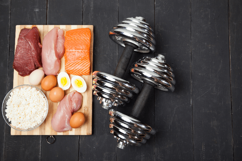 Proteins and dumbbells. Fish, cheese, eggs, meat, chicken and heart on a black wooden background