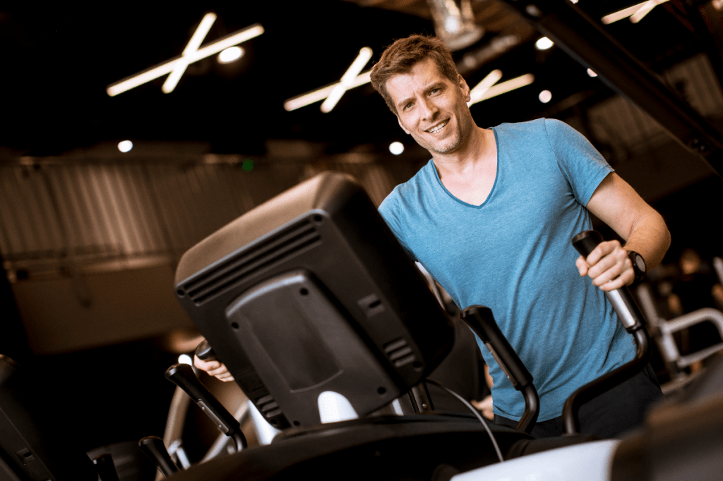 Young man doing exercise on elliptical cross trainer in sport fitness gym club