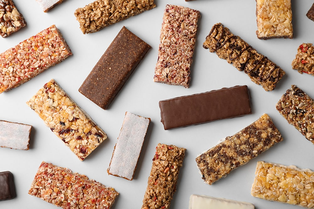 Flat lay composition with protein bars on grey background