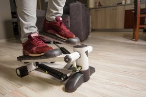 feet of young woman on stepper, sport at home