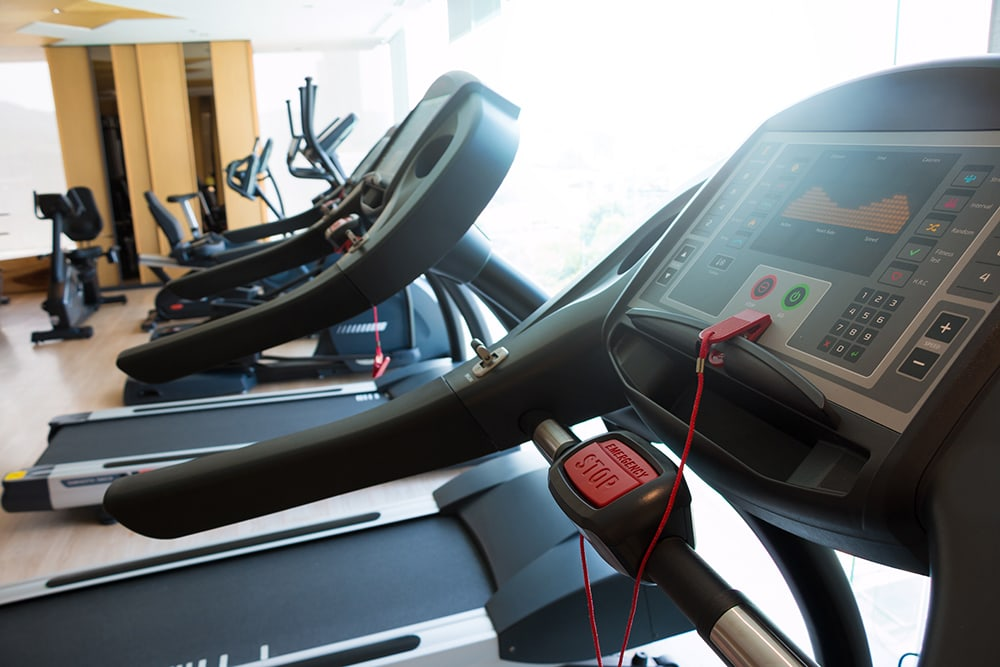treadmill and others equipment in small room gym, in apartment