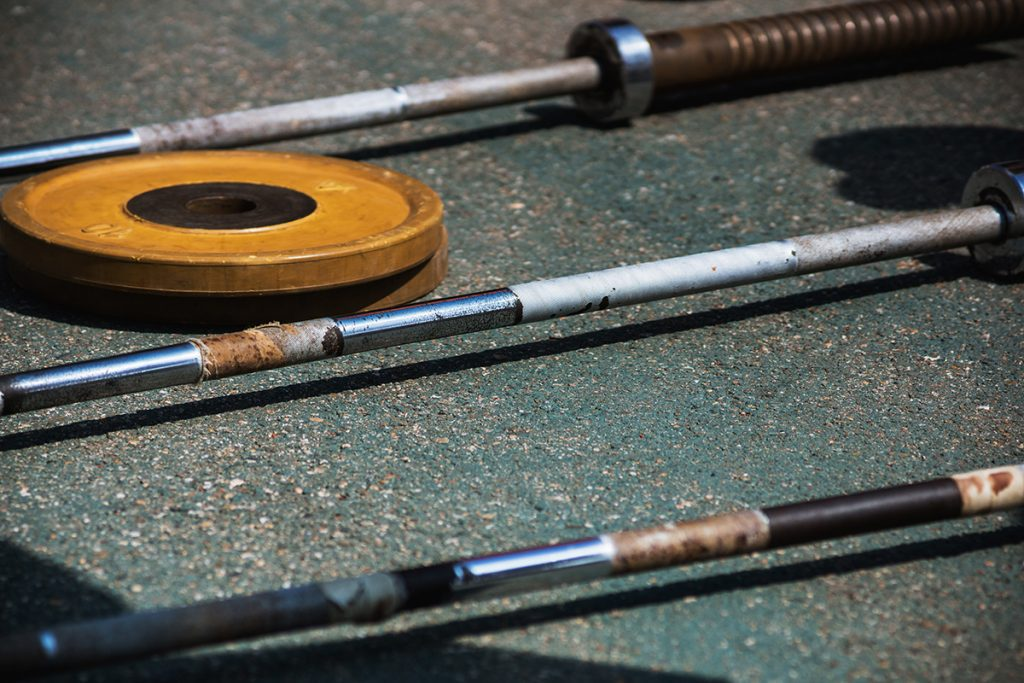 Three metal barbells and two yellow weights lie on the pavement