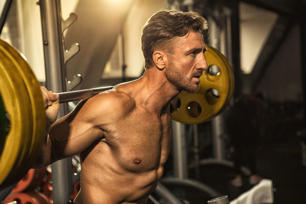 Cropped shot of a handsome mature fitness man performing barbell squats shirtless muscular man with perfect toned body working out at the gym weightlifting bodybuilding gym motivation health concept
