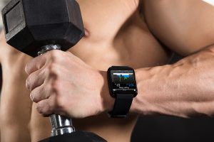 Close-up Of A Athlete Man Wearing Smart Watch While Exercising With Dumbbell In The Gym