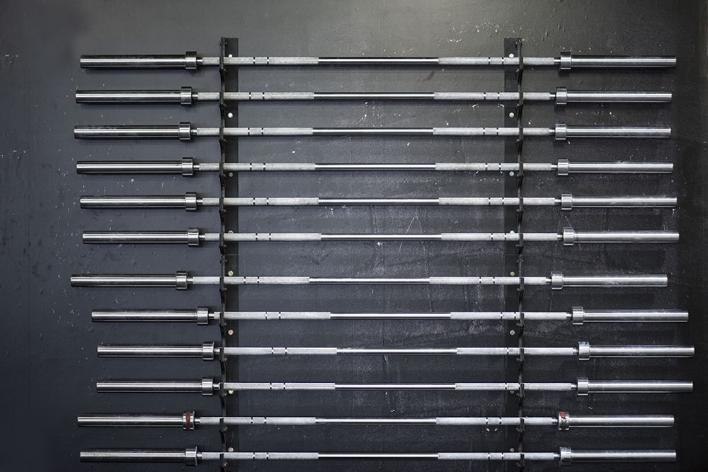 A row of empty Barbells on rack against the wall in Gym with dark gray wall