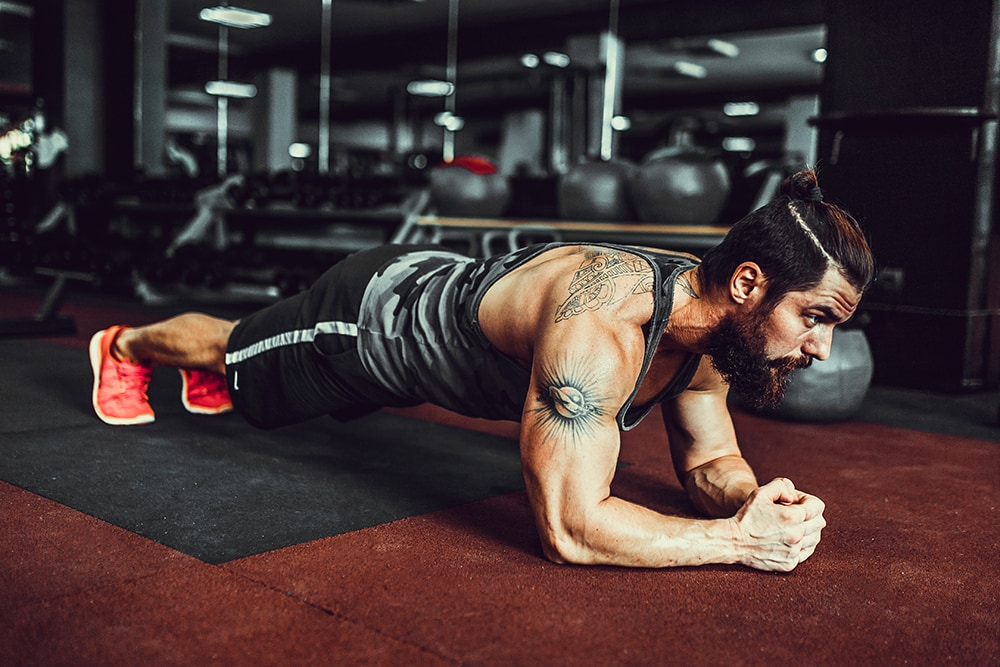 Plank it. Confident muscled young man wearing sport wear and doing plank position while exercising in gym
