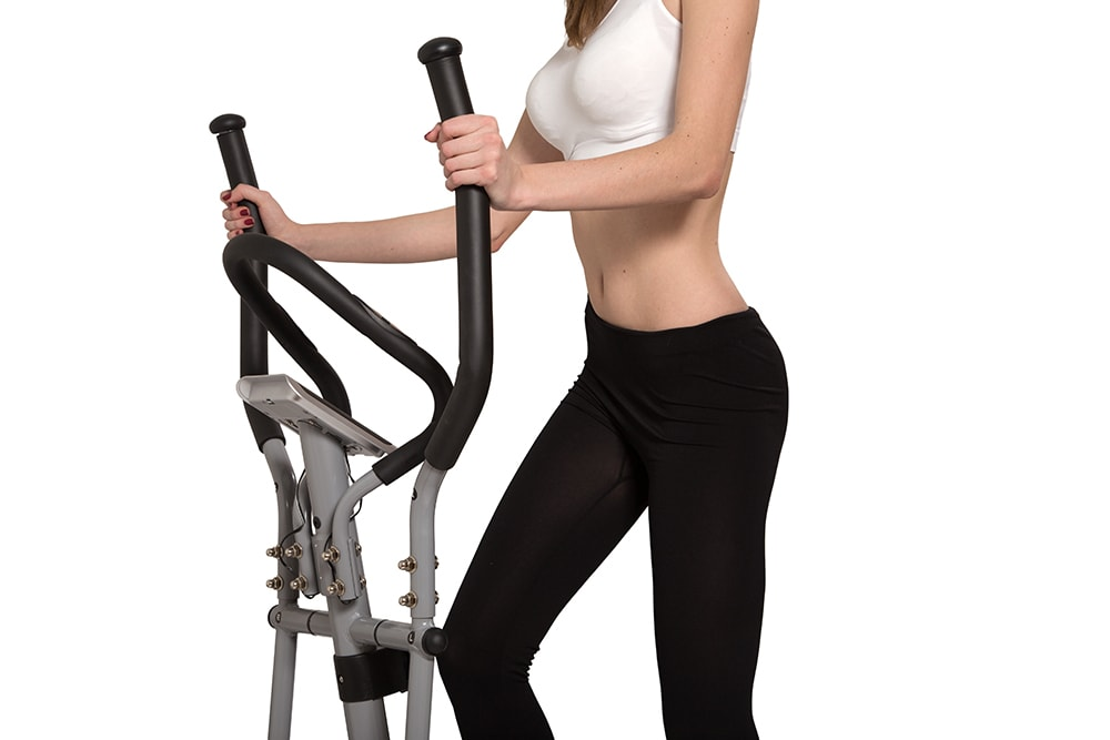 slim unrecognizable woman walks on home elliptical trainer isolated